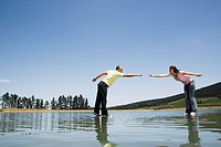 Man and woman standing on water reaching out to each other
