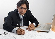 Architect drawing with a pencil on a blueprint
