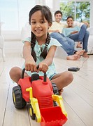 Girl playing with toy dump truck with family in background