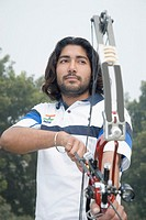 Low angle view of a young man holding a bow and arrow