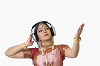 Young woman wearing headphones and performing Bharatnatyam