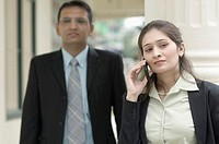 Close-up of a businesswoman talking on a mobile phone with a businessman standing behind her