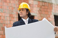 Businessman holding a blueprint and looking away