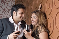 Young couple holding glasses of red wine