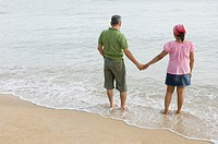 High angle view of a mid adult couple holding hands on the beach