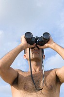 Low angle view of a young man looking through a pair of binoculars