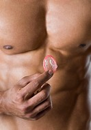 Mid section view of a young man holding a condom