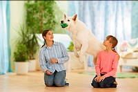 two girls and a White Swiss Shepherd Dog playing with a ball
