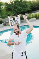 Man dancing by swimming pool