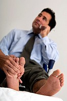 Businessman on phone while getting a foot massage