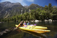 Three people paddling kayaks in mountain lake (thumbnail)