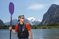 Man holding oar on shore of mountain lake