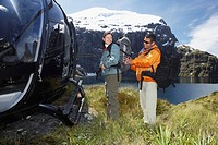 Man adjusting woman's backpack next to helicopter on mountain peak