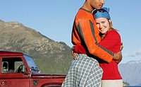 Woman embracing man near jeep by mountains