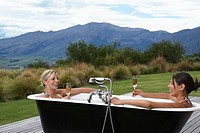 Two women taking bath with champagne on porch near mountains