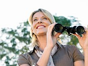 Portrait of adult woman holding binoculars smiling