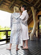 Adult couple in bathrobes embracing on terrace back view