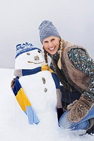 Woman kneeling by snowman on snow_covered hill