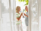 Couple toasting with champagne flutes standing on verandah side view