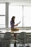 Business woman sitting on conference table side view
