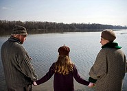 Grandparents holding hands with granddaughter 10-12 by river