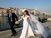 Bride and groom walking Grand Canal, Venice, Italy