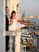 Bride and groom on balcony having a toast Venice, Italy