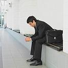 Pensive businessman sitting on bench