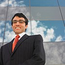 Smiling businessman standing outside building