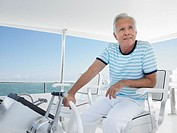 Middle_aged man sitting at helm of yacht