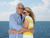 Middle-aged couple embracing against sea portrait (thumbnail)
