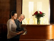 Senior father and daughter playing duet at piano, smiling