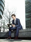 Young man in suit sitting on wall outside office building and reading newspaper