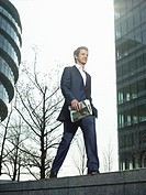Young man in suit walking on wall outside office building holding newspaper