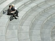 Business man and woman sitting on spiral stairs using laptop elevated view