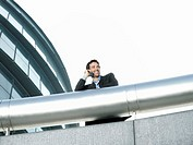 Businessman standing behind pipe outside office building using mobile phone low angle view