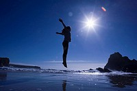 Silhouette of girl jumping on beach