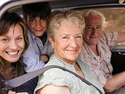 Multi-generational family sitting in car, smiling, portrait