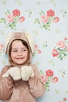 Portrait of young girl 5_6 in bunny costume against wallpaper with floral pattern