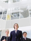 Three business people standing in atrium of office building low angle view