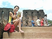 Young woman sitting on steps talking on mobile phone holding guide book