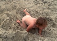 Two year old autistic boy playing in the sand at the beach Children with autism often show unusual sensory and tactile interests and aversions This bo...
