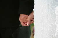 Bridegroom and bride holding hands