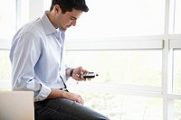 Young businessman using cell phone (thumbnail)