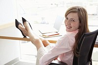 Young businesswoman with feet up on desk