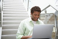 Young man with laptop sitting on stairs