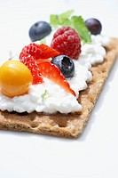 Crisp bread topped with cottage cheese and a variety of berries