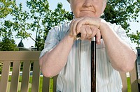 Senior man on park bench with cane