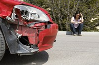 Woman sitting near damaged car