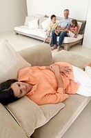 Mid adult woman sleeping on a couch and her husband and two children sitting in the background
